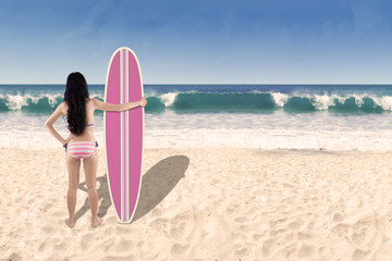 Beautiful young woman with surfboard 1