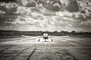 sepia toned light aircraft take-off into dark clouds Wall mural