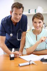 Nurse having doctor signing prescription