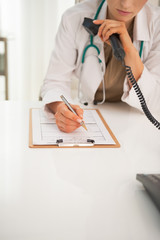 Closeup on medical doctor woman with phone writing in clipboard