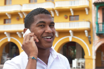 Attractive guy calling by phone in a colonial town
