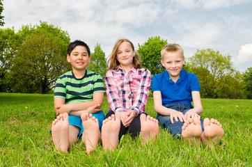 kinder sitzen barfuß im gras