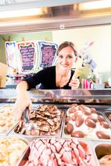 Eisverkäuferin portioniert Kugel Eiscreme in Waffel