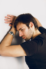 Dismal and sad guy in a black T-shirt and watch on a hand