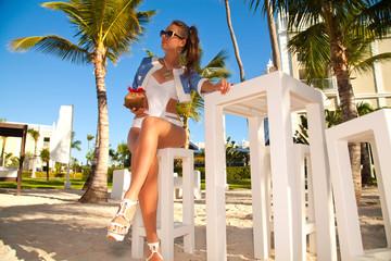 Young sexy woman in white bikini enjoying the sunset