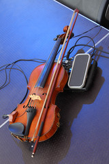 Violin with a pickup. Old violin lying on stage.