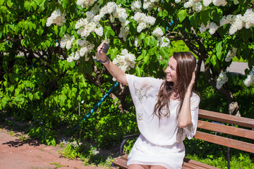 Young woman take photo on her phone at blossoming lilac garden