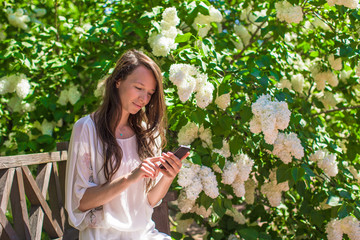 Young woman talking on her phone at flower garden