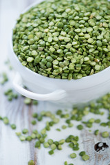 Split dried green peas in a glass bowl, vertical shot, close-up