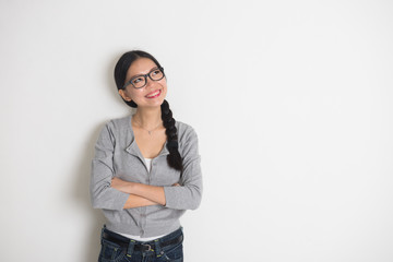 young asian female student thinking with plain background