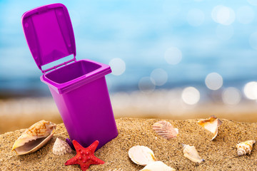 Trash can on clean sand and shells with seascape background