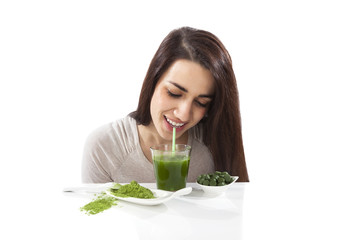 Beautiful girl drinking green juice.