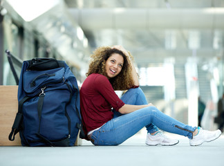Woman smiling with bag at station