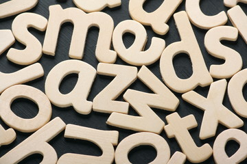 Wooden letters of the alphabet scattered across a blackboard
