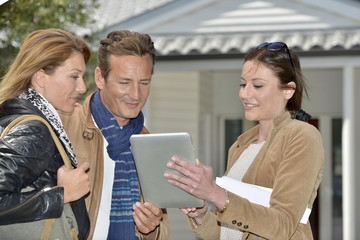 Real-estate agent with tablet showing house to clients