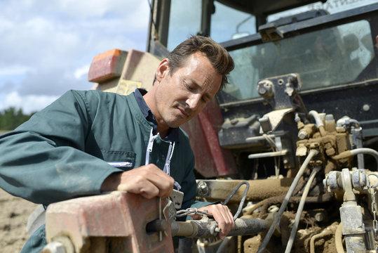 Farmer working on tractor in farming land