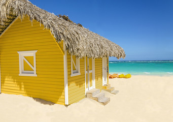 Wooden yellow hut on the beach covered with thatch and kayaks