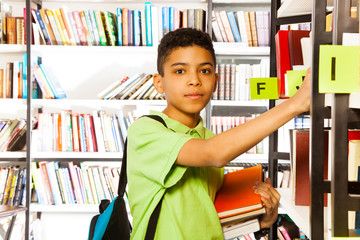 Serious boy looks and searches book on shelf