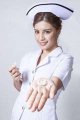Young woman asian nurse holding showing medicine