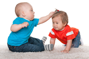 Babies are playing on the carpet