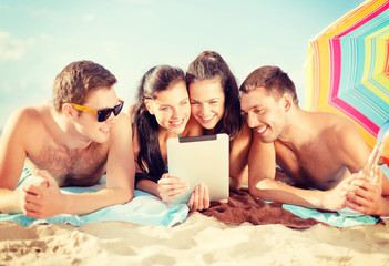 group of smiling people with tablet pc on beach