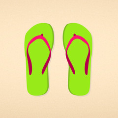 Green with pink striped flip flops on beach sand