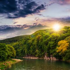 calm mountain river on a cloudy summer sunset