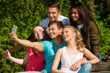 Multi ethnic group of  friends in a park taking selfie
