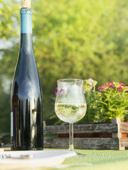 Glass of white wine with bottle on  table in garden