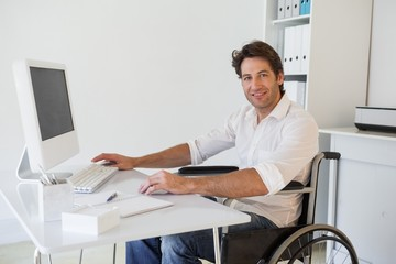 Casual businessman in wheelchair working at his desk