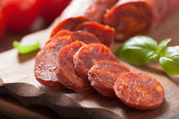 spanish chorizo sausage with basil on chopping board