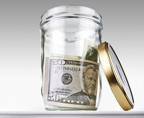 US dollars bank notes in a glass opened jar