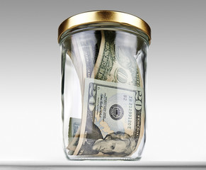 US dollars bank notes in a glass closed jar