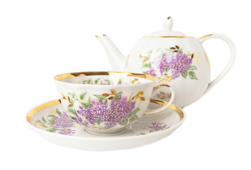 Porcelain teapot, teacup and saucer on white