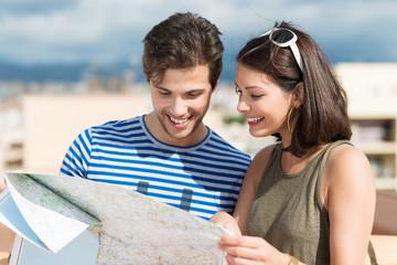 glückliches junges paar schaut auf landkarte