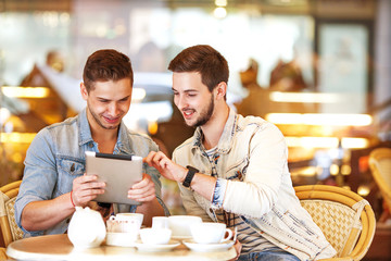 Two young men / students using tablet computer in cafe