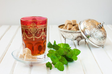 Wall Mural - Moroccan tea with mint and sugar in a glass on a white table