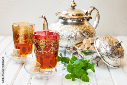 Wall mural Moroccan tea with mint and sugar in a glass on a white table