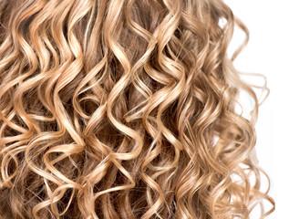 Wavy curly blonde hair closeup. Texture of permed hair