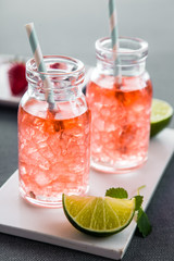 Fruity summer drinks with ice cubes in modern bottles