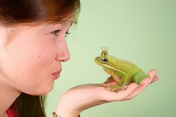 Teenage girl kissing Tree frog (Litoria infrafrenata)