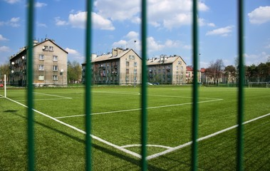 Sport, Soccer field behind the fence, in blocks of flats