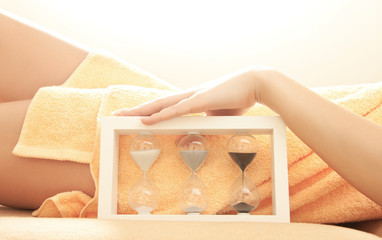 female lying in spa salon with sandglass