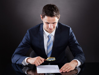 Businessman Examining Contract Paper With Magnifying Glass