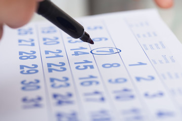 Businessman Marking Date On Calendar In Office