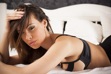 Sexy beautiful brunette woman on the bed