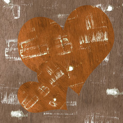 Two wood hearts shape on old wooden board with glue stains