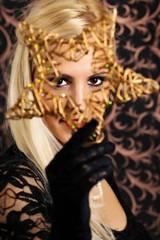 Elegantly dressed light hair model holding wooden star.