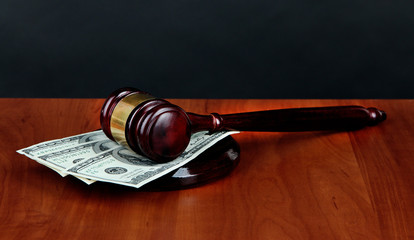 Gavel and money on table on black background