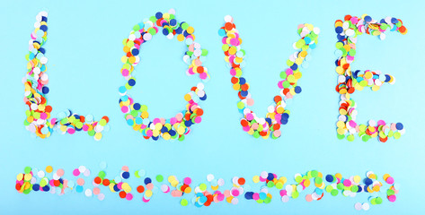 Word Love from confetti on blue background